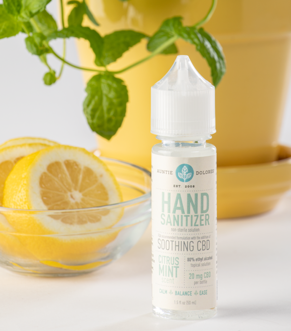 Photo of Auntie Dolores Hand Sanitizer with a bowl of lemons and a mint plant