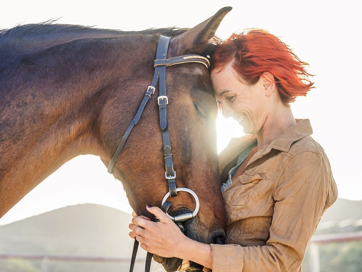 Profile photo of woman snuggling her horse who feels calmer after taking Treatibles hemp CBD oil for horses