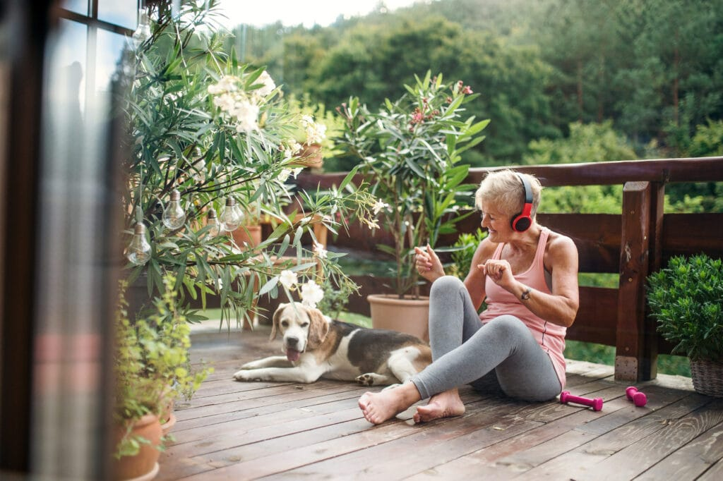 A mature woman with headphones outdoors on a terrace resting with senior dog after exercise