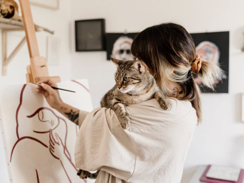 Young female artist painting in her studio holding cute cat over her shoulder