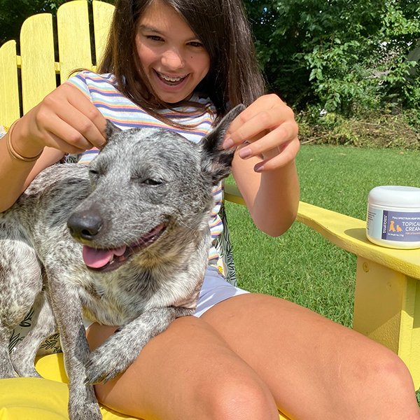 image of little girl gently applying Treatibles Topical Cream to her gray dog's ears.