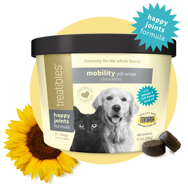 Light yellow canister of Treatibles Happy Joints Mobility Pill Wrap Chewables featuring a black cat and golden retriever along with two Chewables placed by the right front and a sunflower by the left front